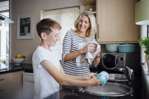 Mother and son washing dishes and laughing