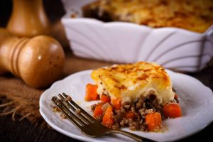 Shepherd's pie with beef, carrots and mashed potatoes served on a white plate