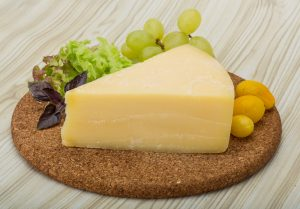 Triangle of Dubliner Irish cheddar cheese on a cork plate with grapes and lettuce