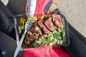 Woman wearing athletic shoes eats lunch.