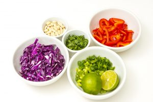 Chopped veggies in white bowls.