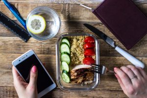 Busy woman eats healthy lunch at desk.