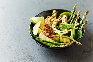 Bowl of grilled chicken, asparagus, avocado, lime