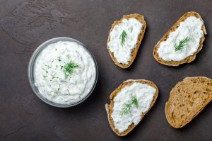 Tzatziki sauce in bowl and on bread