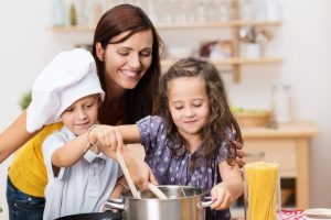 mom and children stirring pot's contents