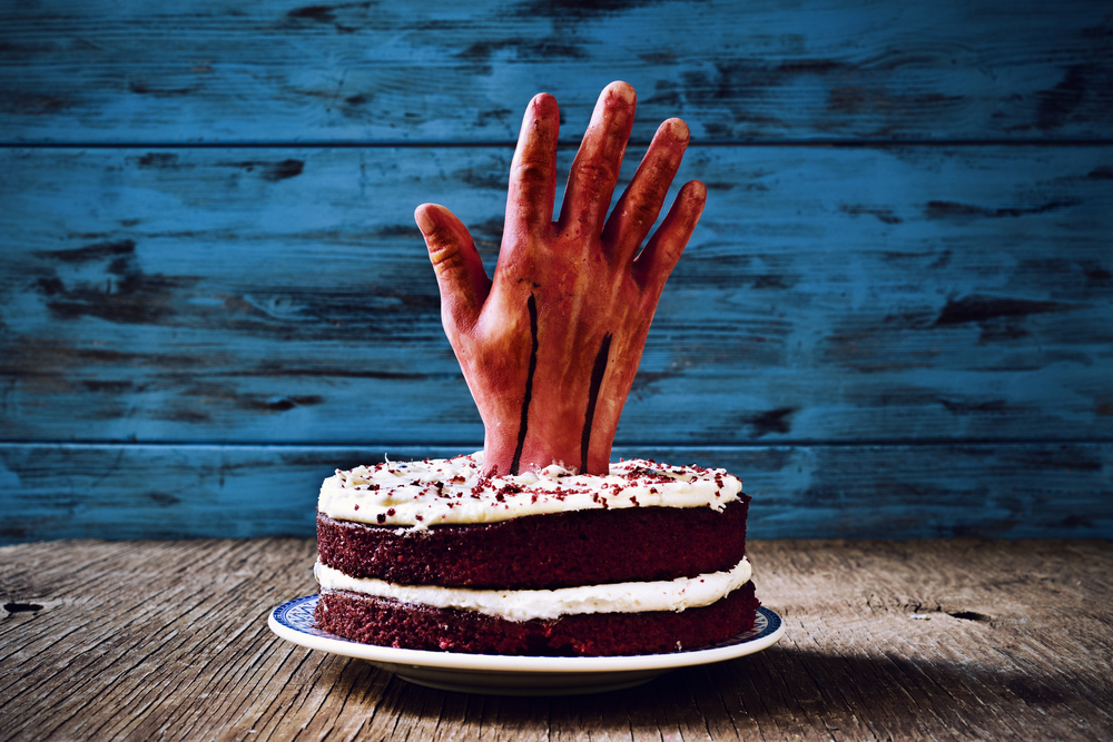 Bloody prop hand rising from red velvet cake.