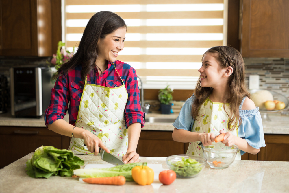 Mother and daughter peel vegetables for soup.