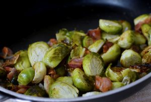 Brussels sprouts roasting in pan with bacon.