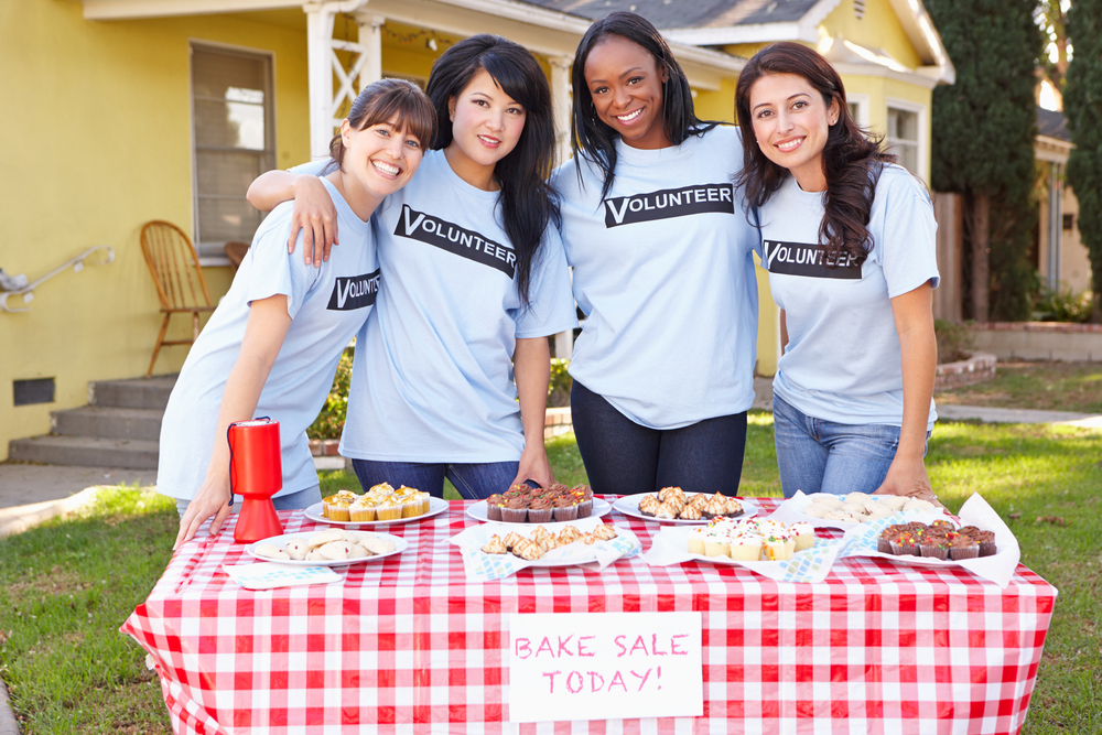 Four women posing together outside in front of a table that is for a bake sale.