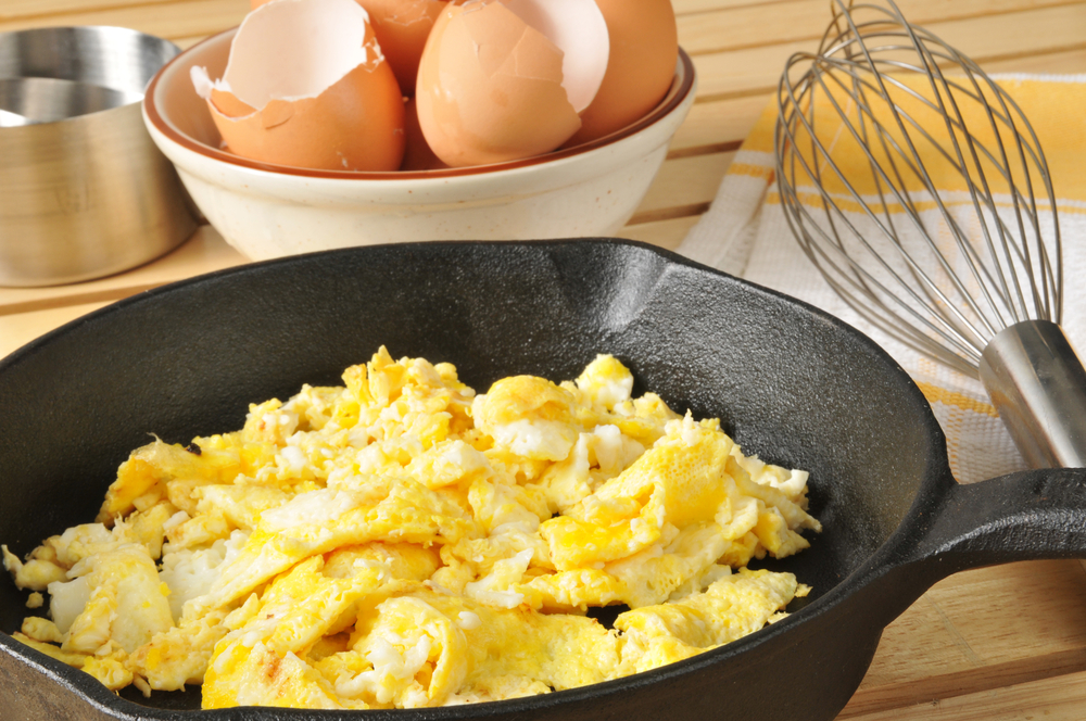 A skillet with scrambled eggs, a clean whisk, and broken eggs shells are sitting on a table.