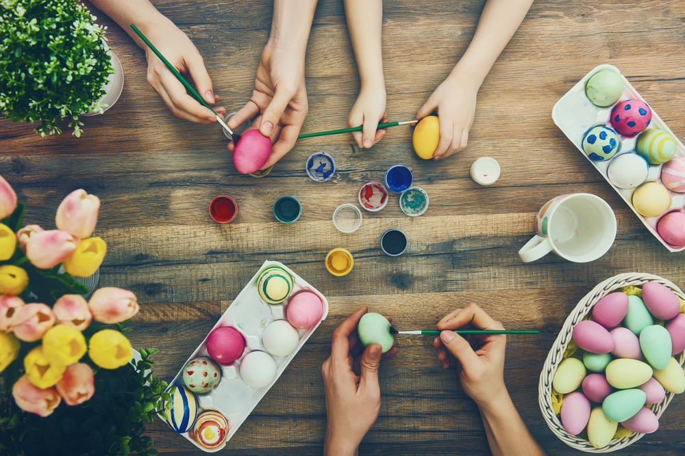 several hands painting boiled eggs on a wooden table.