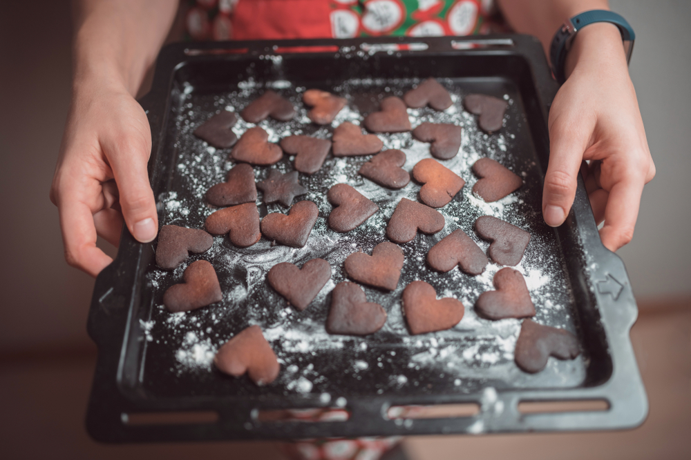Girl holds tray of burned cookies.