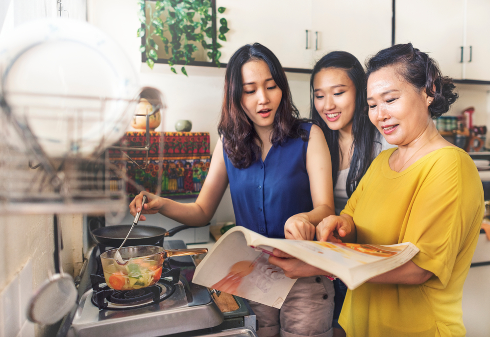 Mother teaches daughters to cook.