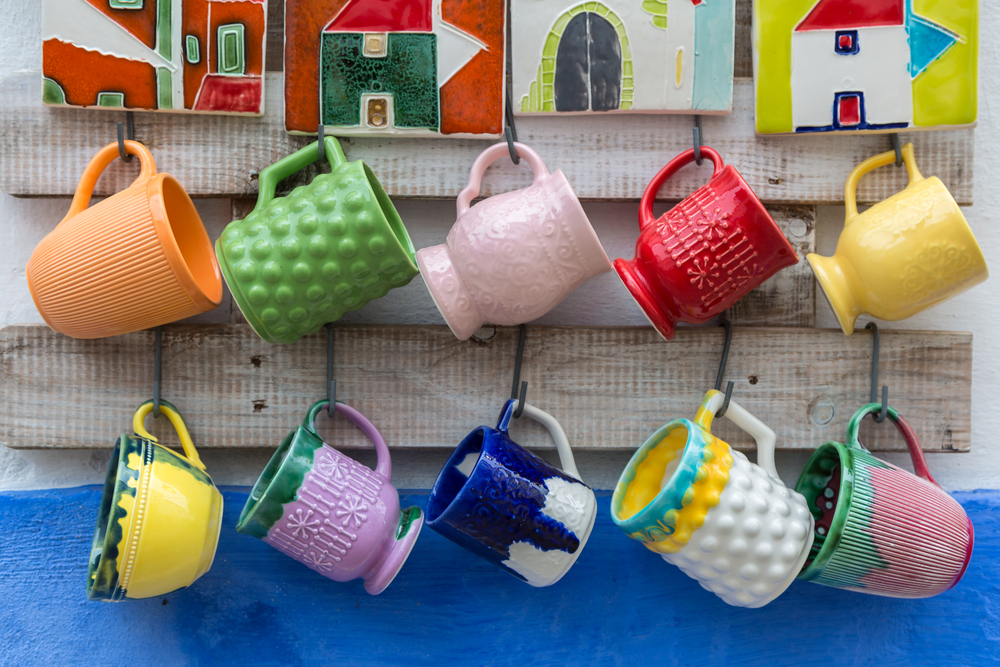 Bright mugs hanging on wall.