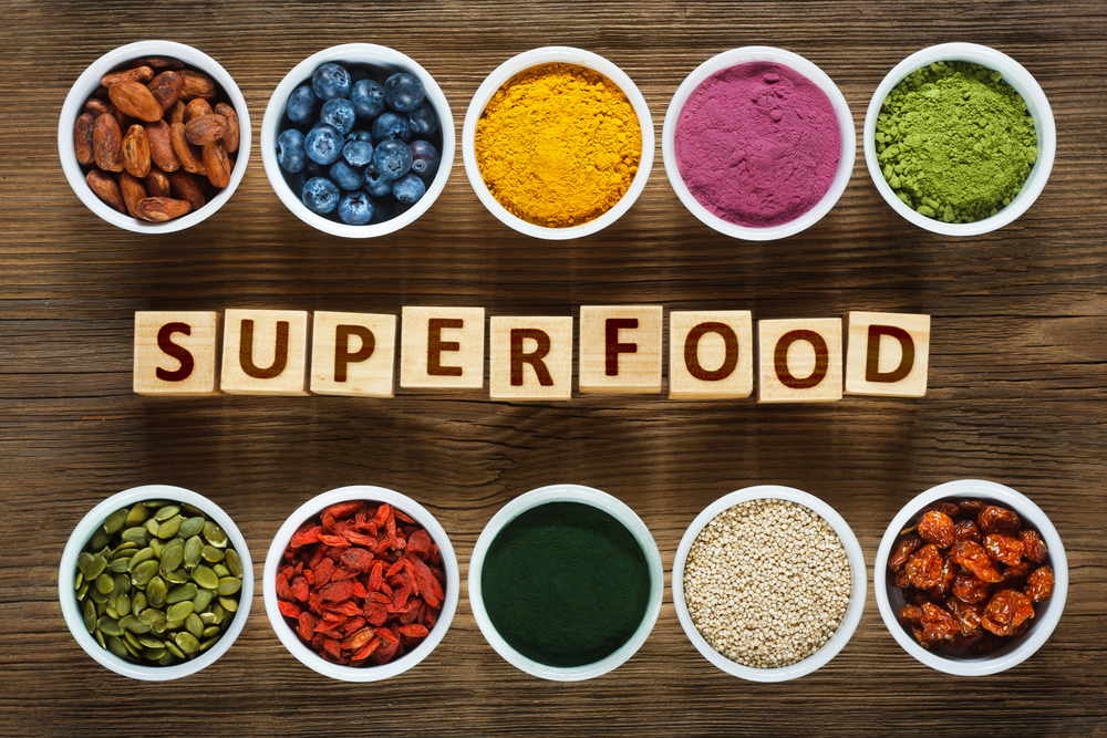 "Ramekins of superfoods set out to border Scrabble tiles spelling ""superfood"""